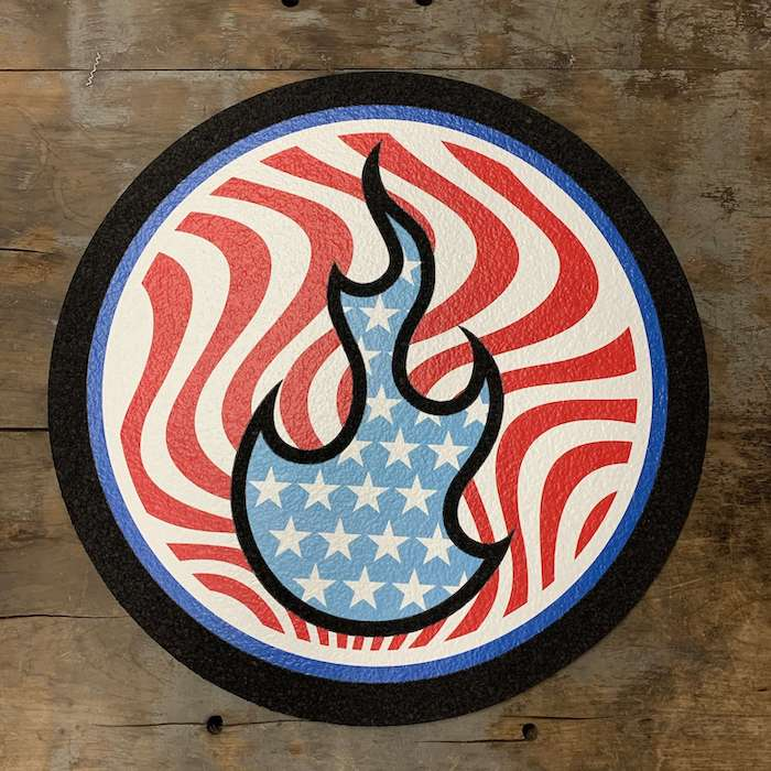 Stoked 17 inch circular mood mat on wood background with stoked flame logo in blue and white stars, background red wavy lines