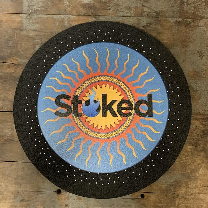 Stoked 17 inch circular mood mat on wood background with Stoked sun logo in orange and blue