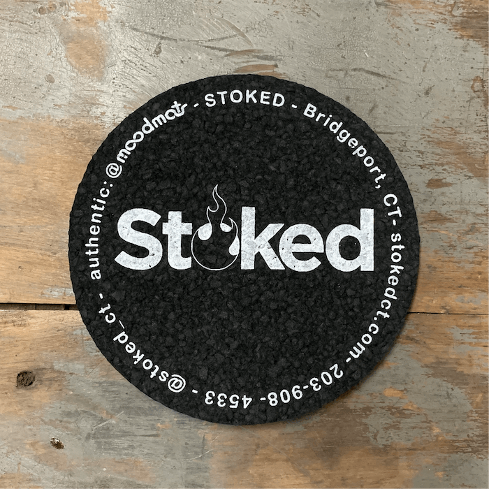 Stoked 5 inch coaster mood mat, black circular mat with Stoked logo in the center; written along circular edge is Stoked, Bridgeport CT, stokedct.com, 203-908-4533, @stoked_ct, @moodmats