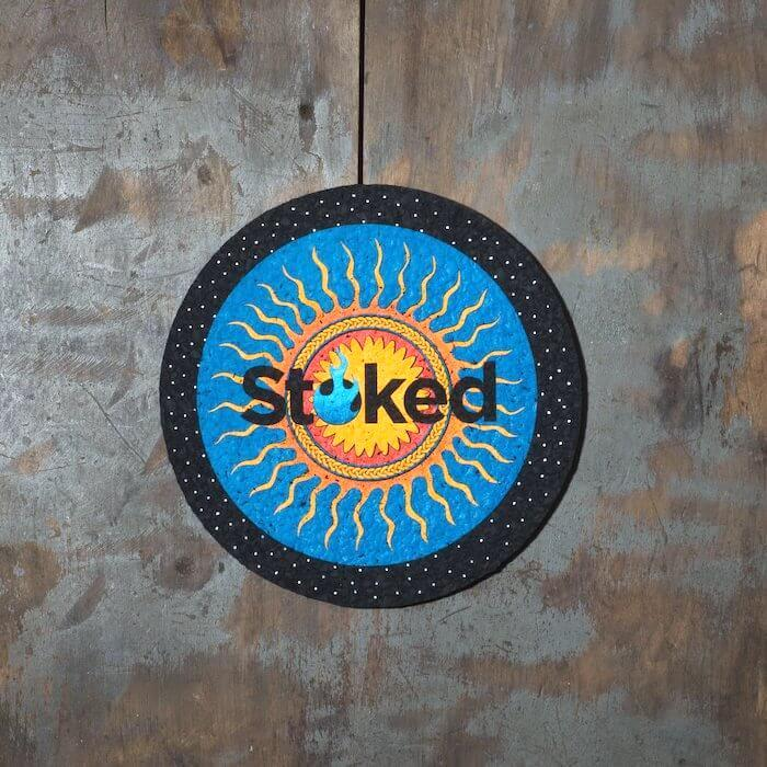 Stoked 8 inch mood mat on wood background. Blue and yellow sun logo centered