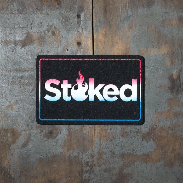 Stoked 8x5 inch black mood mat on a wood background. Stoked logo and outer outline are red fading to white fading to blue