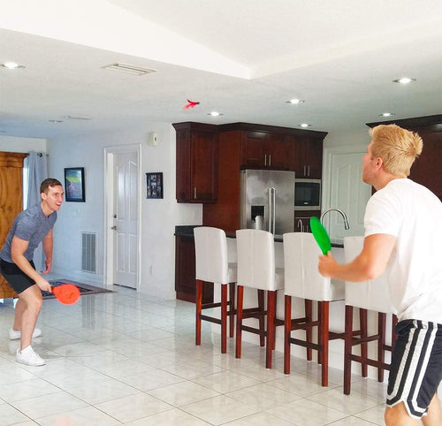 Friends playing Jazzminton paddle ball indoors by the living room and kitchen