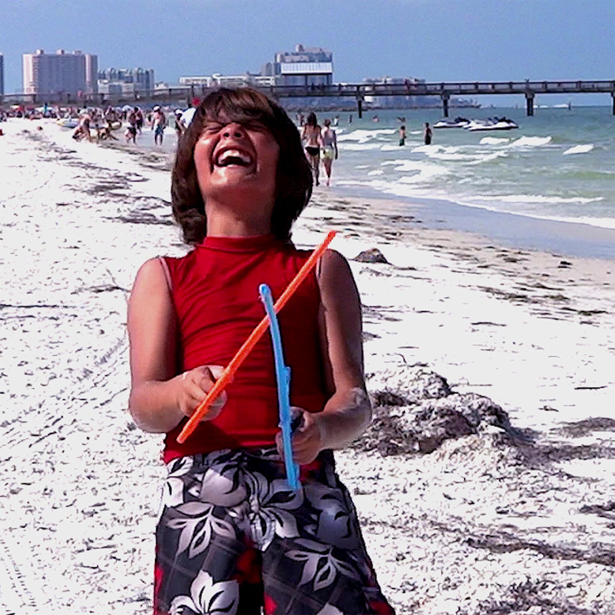 Kid laughing having fun playing RingStix at the beach