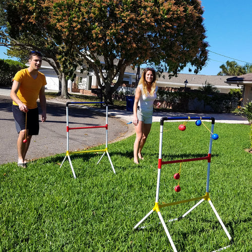 siblings playing ladder golf set in front yard