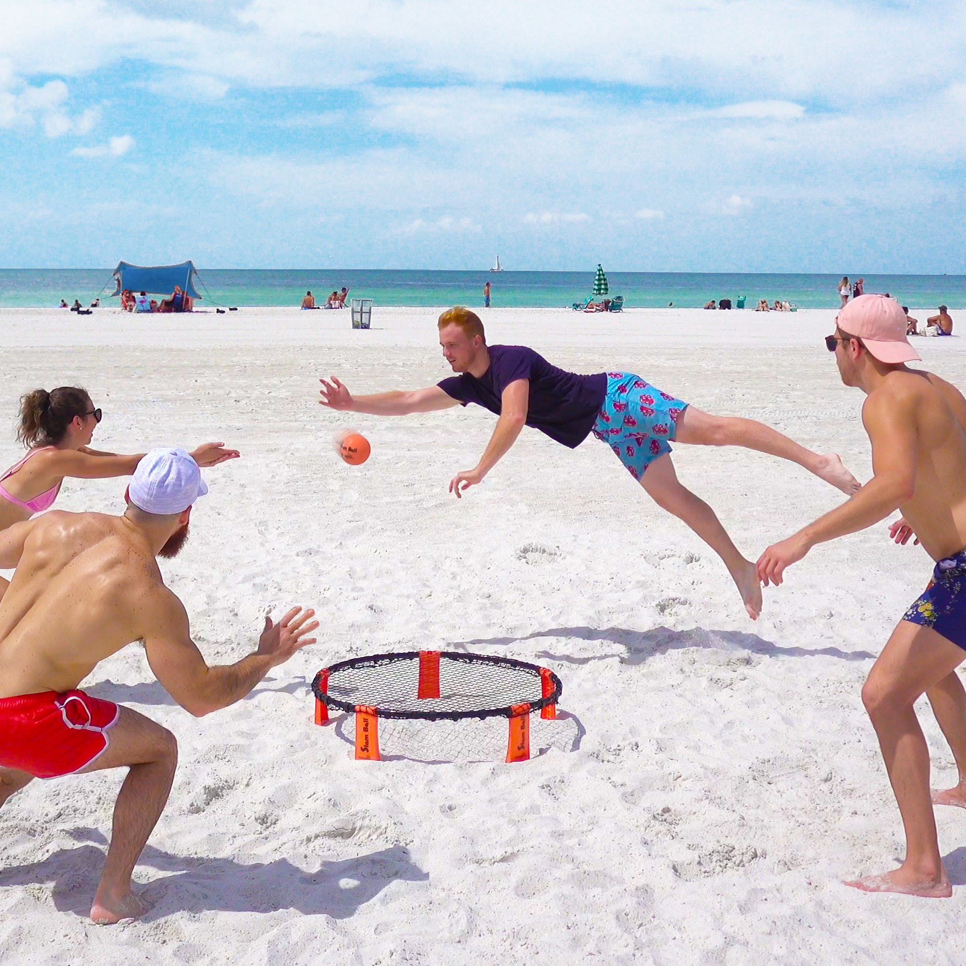 Friends playing Slam Ball at the beach