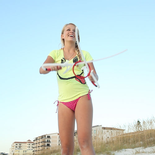 Girl playing Ringstix outdoor game at the beach