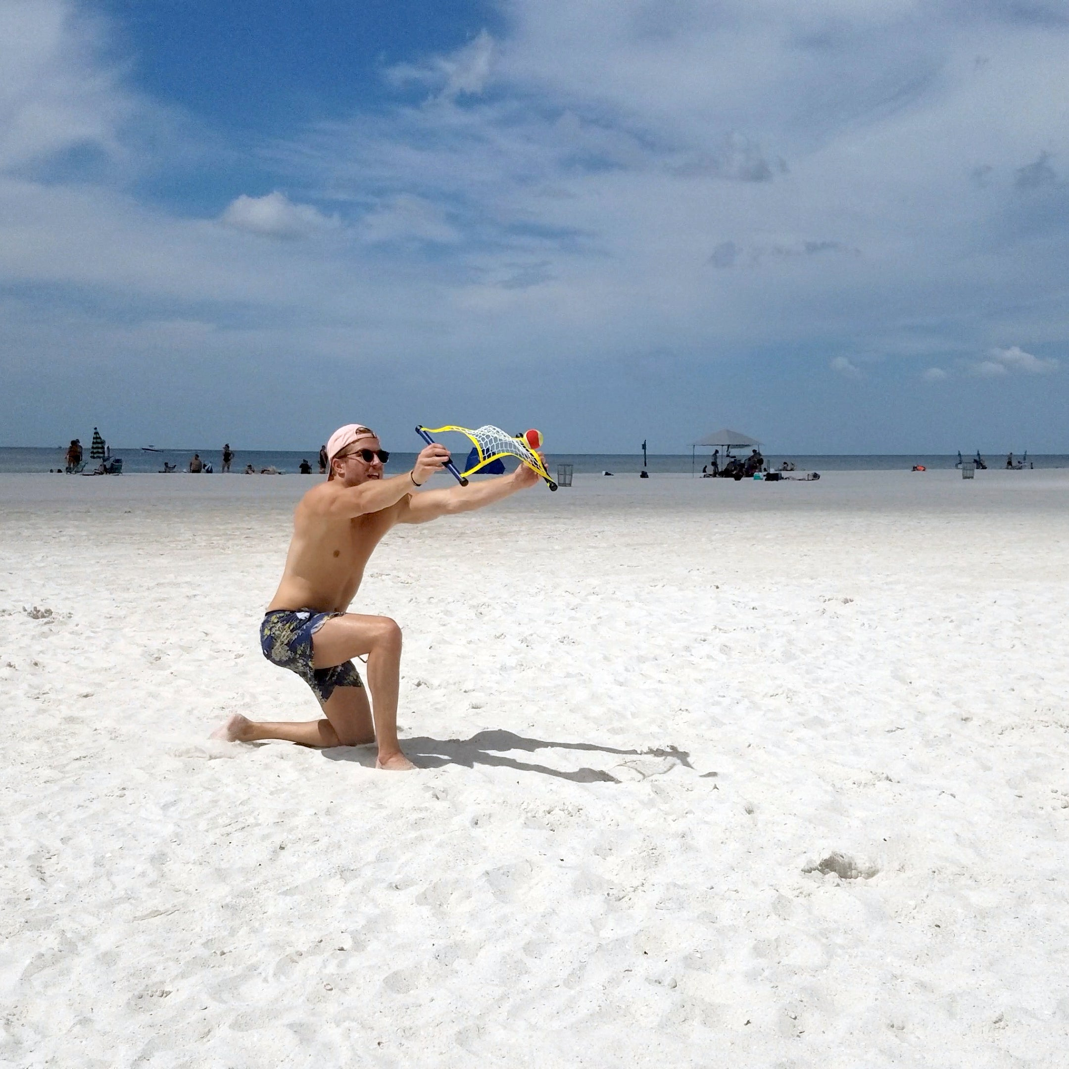 Guy hitting ball off net playing Switch Ball on the beach