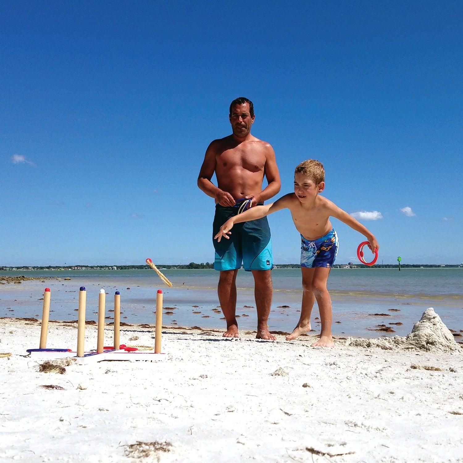 Dad and son playing Ring Toss at the beach having fun by Funsparks