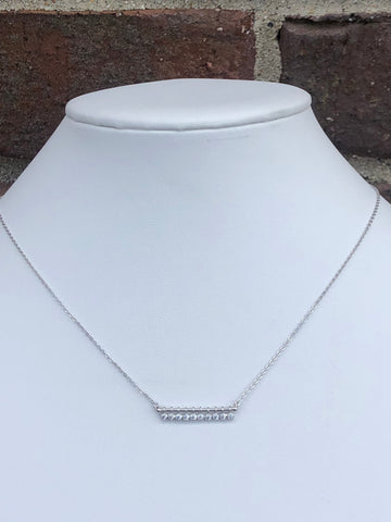 Bar necklace with ten round cubic zirconia stones underneath the bar.   The necklace is sterling silver.