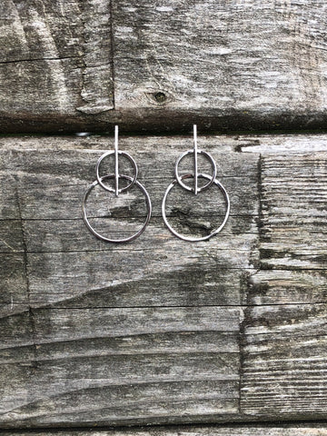 EEarrings are a double hoop with a bar gong down the middle.   Earrings are sterling silver with a post back closure.