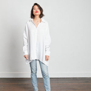 Model faces the camera wearing white oversized linen boyfriend shirt wearing jeans and bright red lipstick