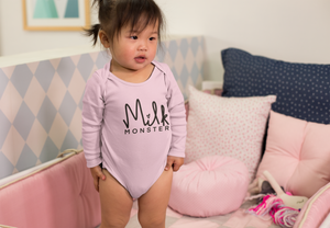 "Pink long sleeve breastfeeding onesie that says ""Milk Monster"" worn by a baby/toddler girl."