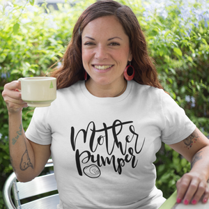 "Woman holding a cup and smiling while wearing a white t-shirt that says, ""Mother Pumper""."