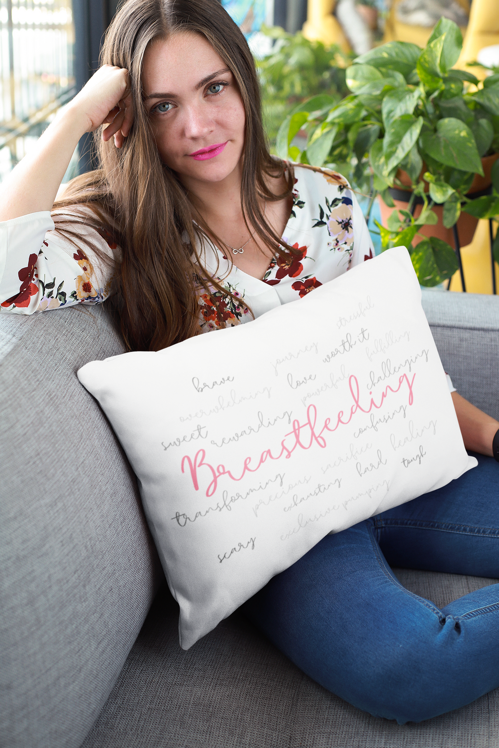 Woman holding pillow with the Breastfeeding surrounded by powerful words to describe it.