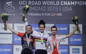 female bike racers standing on podium in rainbow jersey