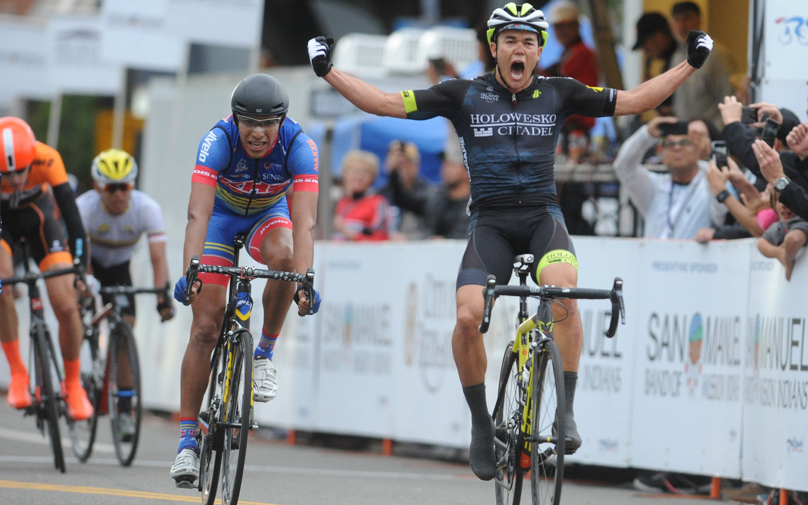 bike racer raises arms in victory at finish line. The Holowesko-Citadel  men s pro cycling team ... 348bedb55