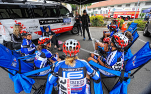 Women bike racing team sits in chairs