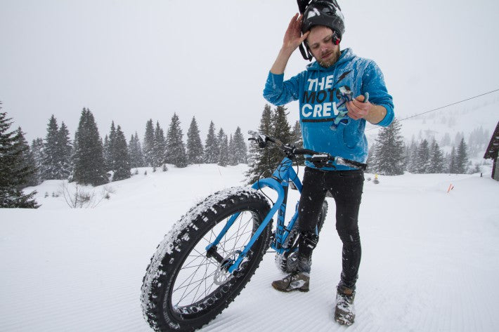 man in blue sweater with fat bike in snow