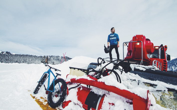 man with bicycle on top of snow plow