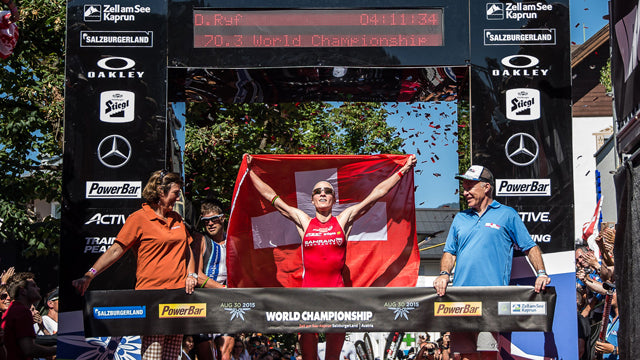 female triathlon racer wins finish line