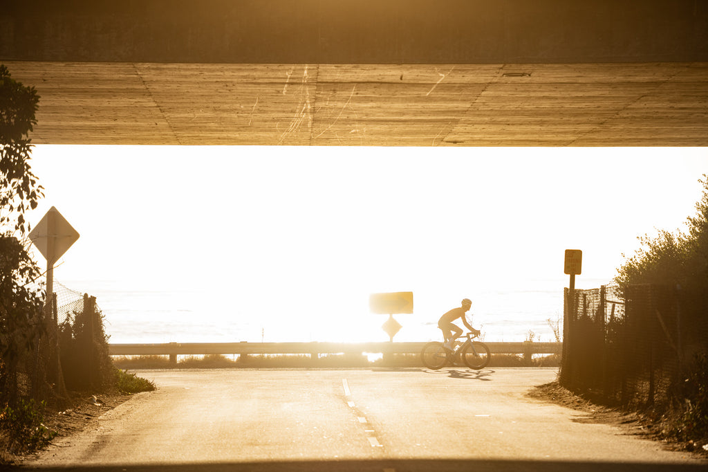 cyclist at sunset by ocean