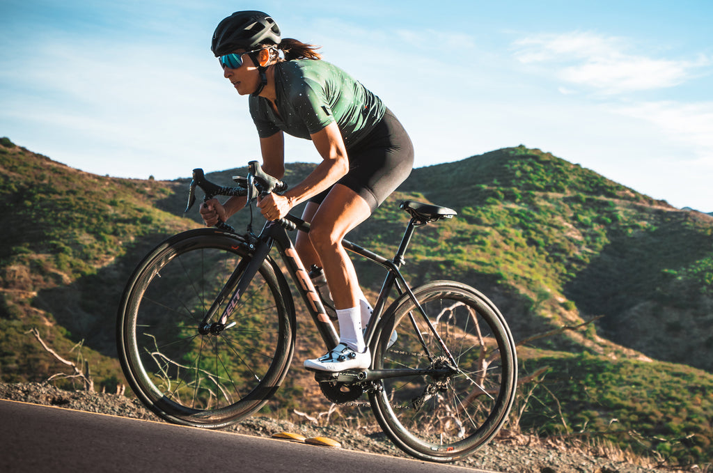 female cyclist on a road bike climbing