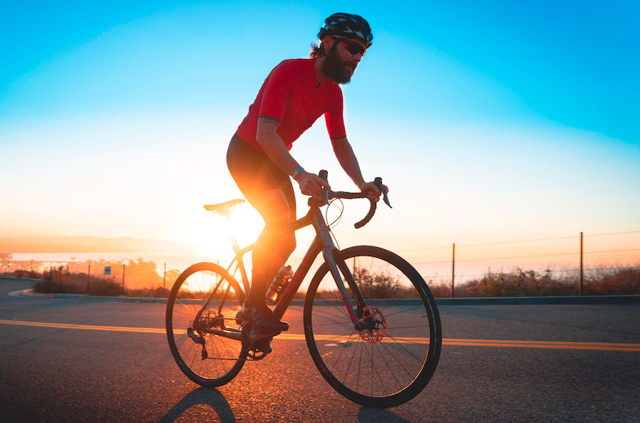 male cyclist riding bicycle at sunset in california