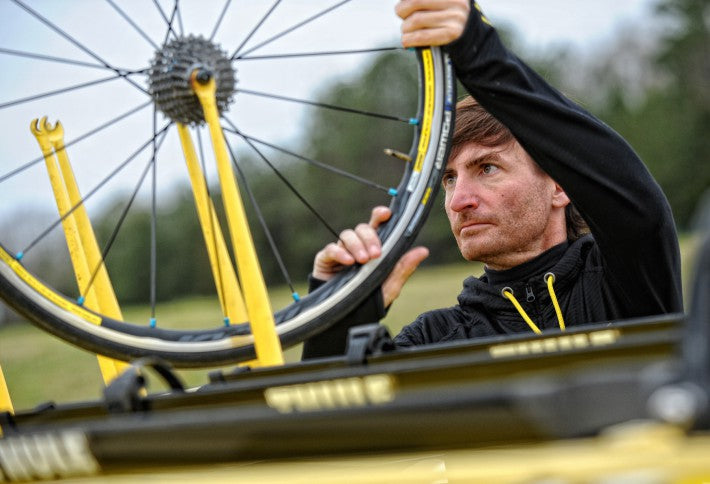 man holding bicycle wheel on car yellow