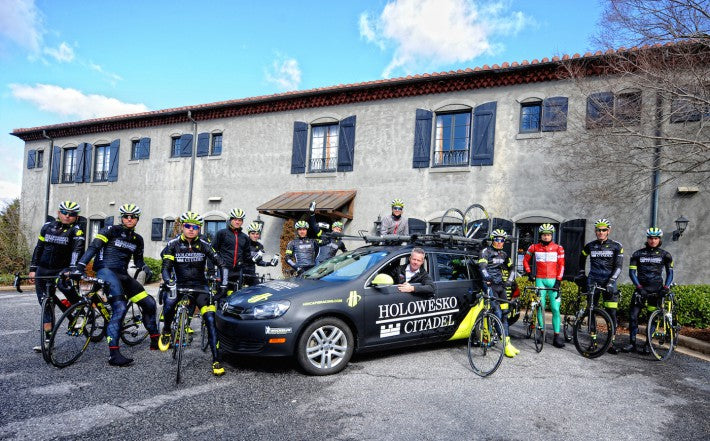 bicycle racers team portrait with car