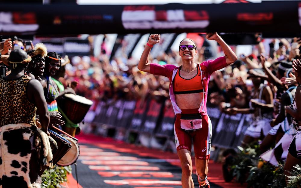 female triathlete crossing finish line