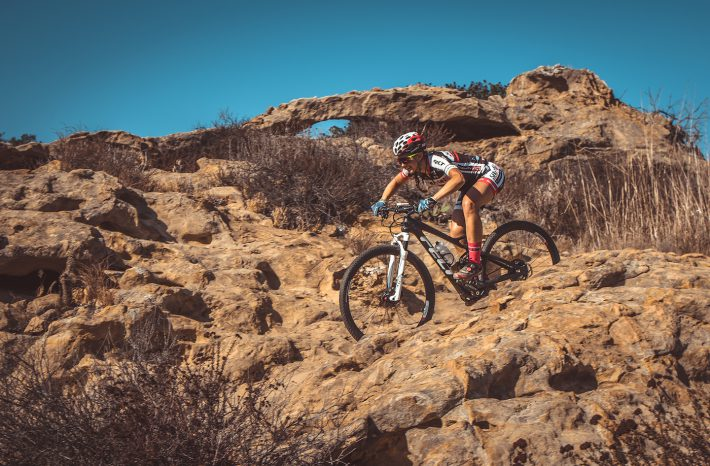 female mountain biker rides downhill