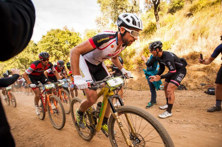 mountain bike racer leads through fans