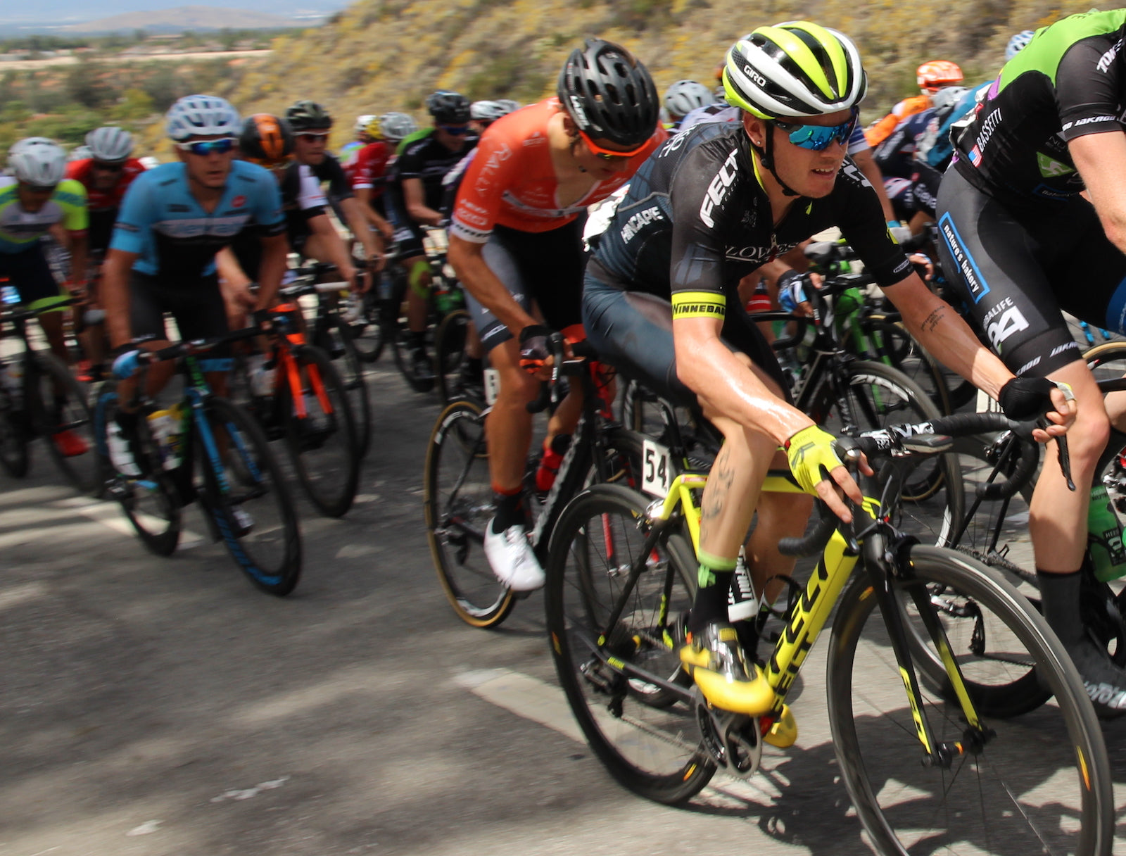 bike racer climbs hill in a group