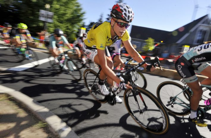 female bike racer corners in group yellow jersey