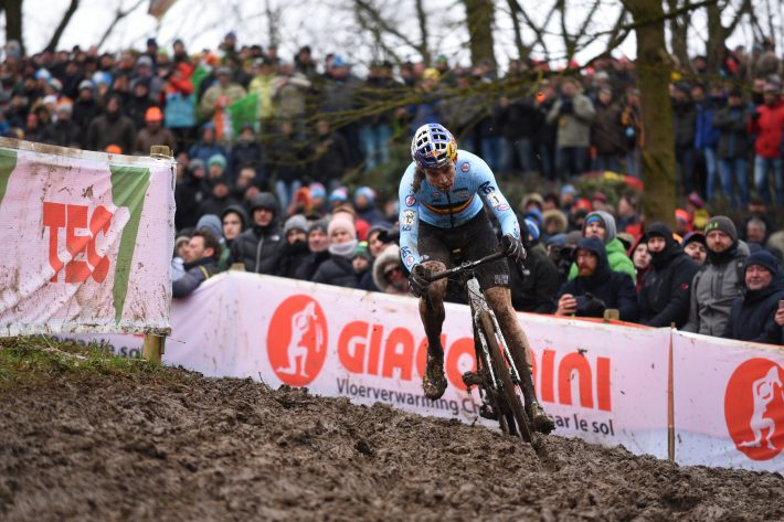 Muddy bike racer corners in front of a crowd