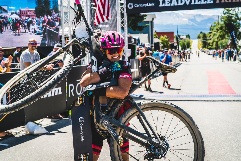 woman hugging mountain bike leadville race