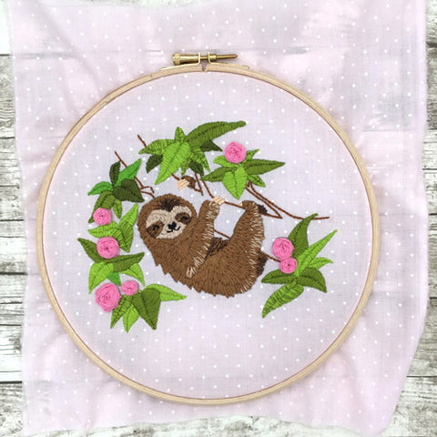 Finished embroidery of sloth on pink fabric
