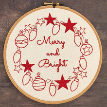 Load image into Gallery viewer, Close up of hand embroidered Christmas wreath stitched from a Lazy May Iron on embroidery transfers.