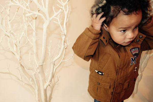 A toddler in a brown coat walking between two white trees and pulling his hood up.