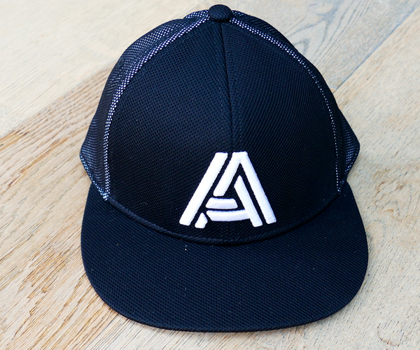 A hat that has been placed on a wooden floor, it is black with a white A on it.