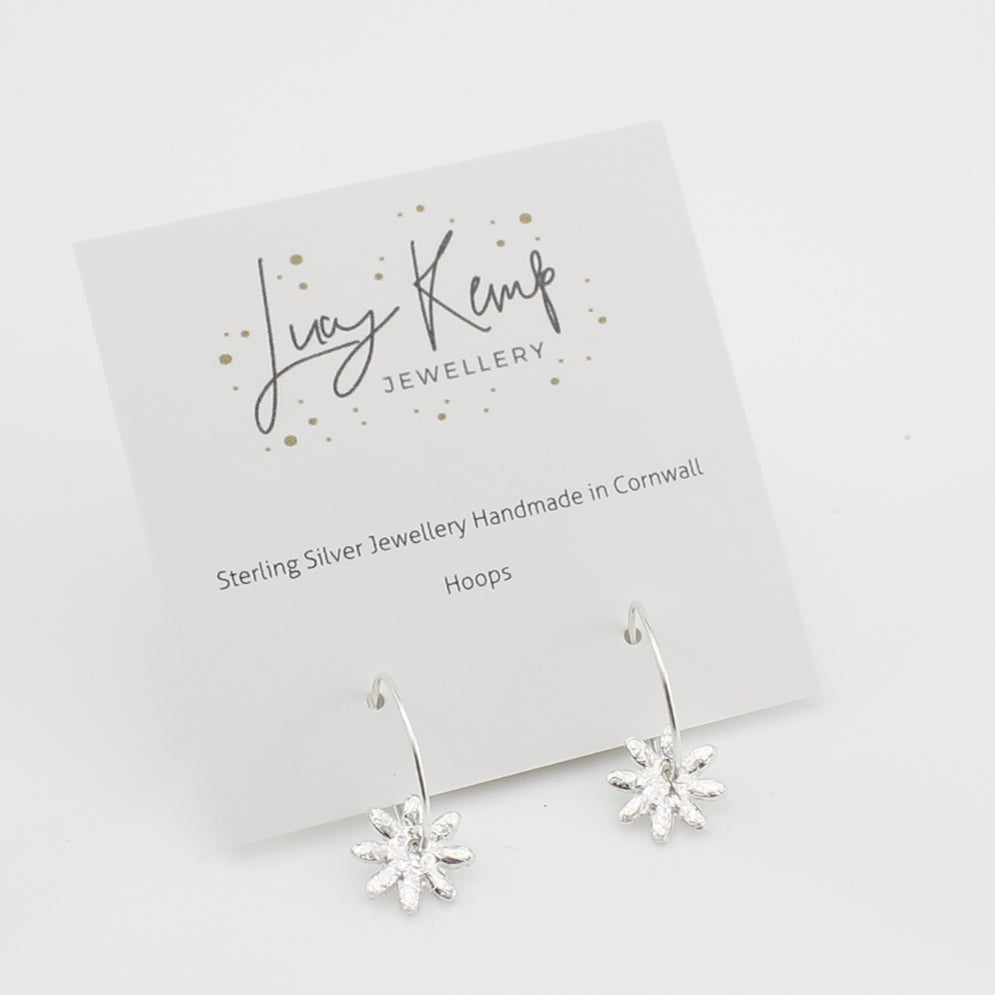 Sterling silver handmade daisy charm hoops by Lucy Kemp Jewellery in Cornwall