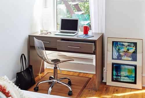 Sleek window setting featuring Baru desk with clear office chair