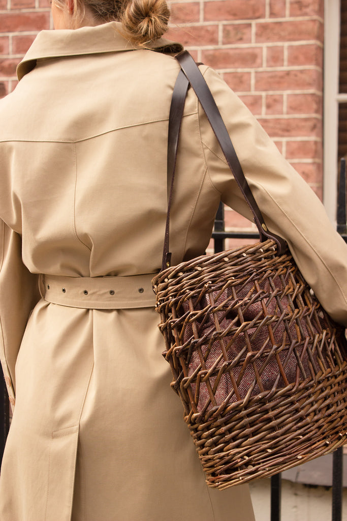 girl in brown mac coat with willow basket