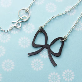 Ribbon bow pendant in blackened sterling silver.