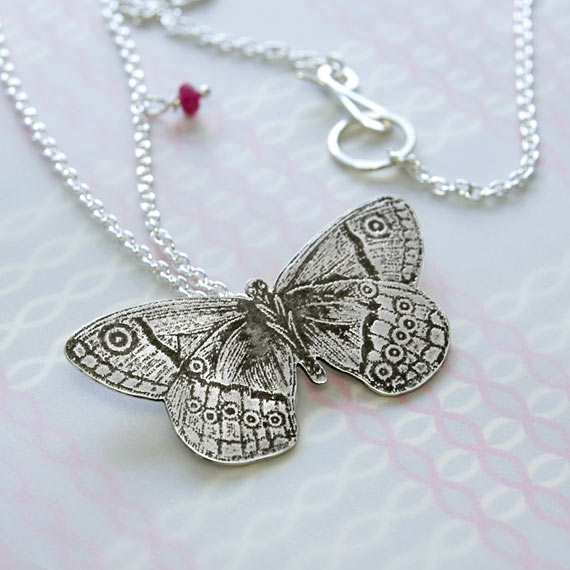 Etched butterfly pendant in sterling silver with ruby gemstone.