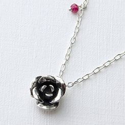Rose pendant handmade in sterling silver with a ruby gemstone.