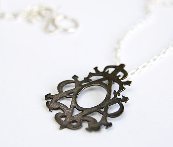 Victorian-inspired handmade silver pendant.