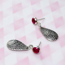 Lace pattern etched teardrop earrings with lab grown ruby gemstone settings.