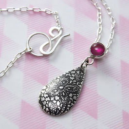 Lace pattern etched teardrop pendant with a lab grown ruby gemstone setting.
