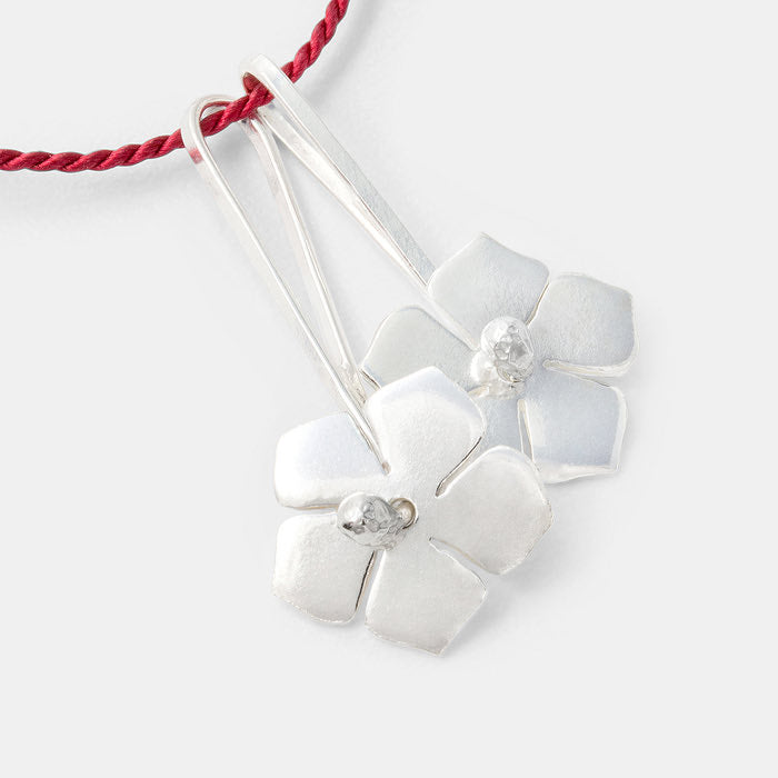 Sterling silver forget-me-nots pendants on red silk necklace.